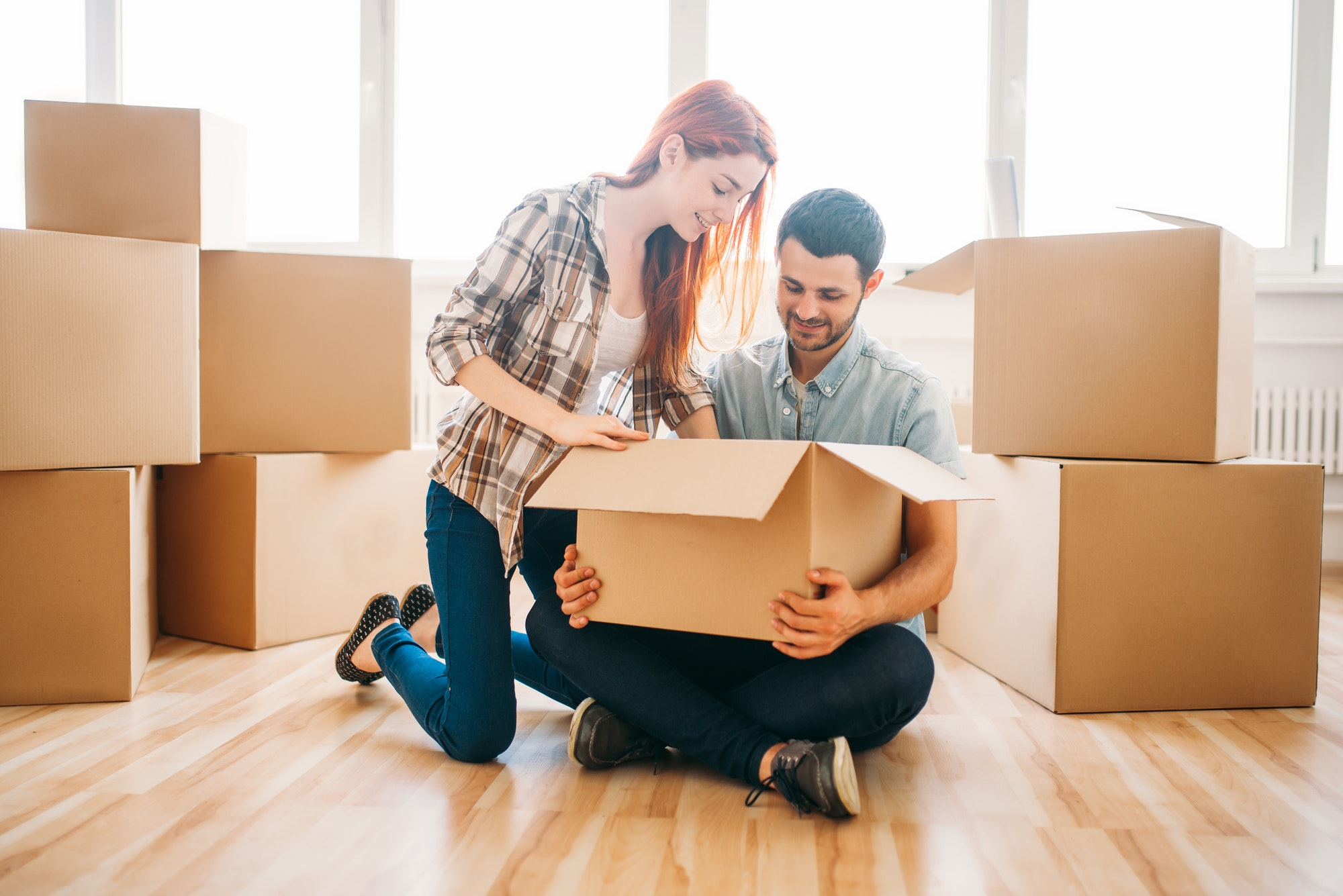 Couple unpacking boxes with property, housewarming